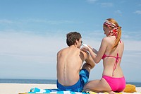 Woman applying sunscreen on man's back at beach