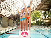 Boys standing on winners podium by swimming pool portrait