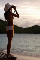 Young woman using binoculars on beach, St. John, US Virgin Islands, USA