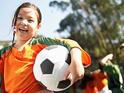 Girl holding soccer ball portrait, low angle view