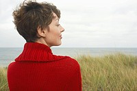 Woman in cardigan at beach rear view