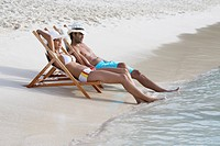 Young couple on lounge chairs on sandy beach