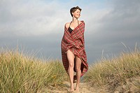 Woman wrapped in blanket walking on path