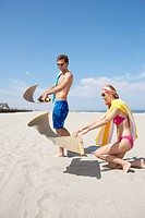 Young couple spreading beach mats on beach, Spring Lake, New Jersey, USA