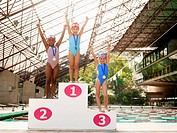 Girls in swimming costumes celebrating on winners podium portrait