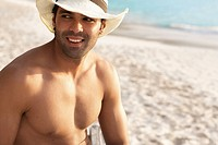 Young man wearing straw hat on beach
