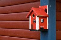 Close_up of birdhouse Rödmålad fågelholk av trä hänger på blå och röd husvägg