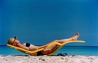 Woman relaxing on lounge chair at beach kvinna solar på strand
