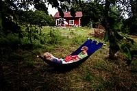 Two people lying on hammock in garden Mamma och barn ligger i hängmatta på torpet.