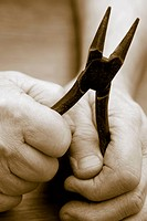 Close_up of a person´s hands holding a pair of pliers