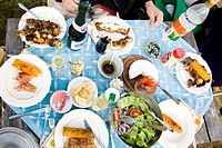 Elevated view of person eating food at dining table Ett matbord utomhus på sommaren med blå duk, lax, grillspett, sallad, majskolvar och brieost och a...