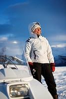 Man wearing winter clothes standing near snowmobile Kvinna i vit jacka står och pimplar vid en skoter i ett vinterlandskap