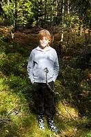 Pojke står i skogen med händerna i fickorna, närbild. Boy Standing In Forest With Hands In Pocket, Close_Up