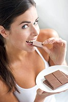 A woman biting into a piece of chocolate