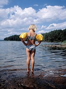 Flicka med armkuddar står vid sjökanten. Close_Up Of Girl With Water Wings Standing At Sea_Shore