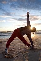 Kvinna utövar yoga på stranden i solnedgången. Woman Doing Yoga On The Beach In Sunset