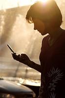Silhuett Av Ung Kvinna Med Mobiltelefon, Woman Standing With Holding Mobile Phone