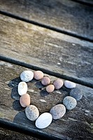 Close_up of Pebbles arranged in heart_shape on wooden table Stenar ligger på en brygga och formar ett hjärta