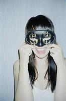 Ung leende kvinna i maskeradmask, närbild. Close_Up Of Woman Wearing Fancy Dress Mask, Smiling