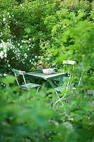 Liten Undangömt Sittplats I Grönskande Trädgård, Chairs And Table In Garden
