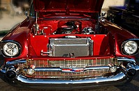 The front of a 1957 chevrolet with the hood open