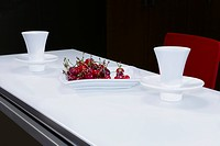 Cherries with tea cups on a table