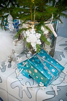 Christmas Ornamental Hanging On Christmas Tree With Gift Wrapped In Blue Paper