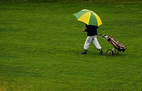 Golfspelare med paraply drar golfbag på golfbana. Man With Umbrella Pulling A Golf Bag On Golf Course.