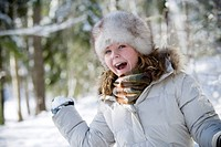 Glad flicka med pälsmössa lelekr i snön Close_Up Of Girl Playing With Snowball, Portrait