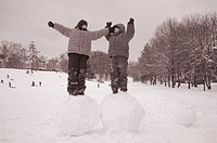 Two boys standing on big snoww balls