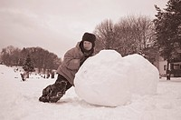 Boy rolling big snow ball