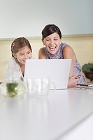 Mother and daughter looking at laptop and laughing