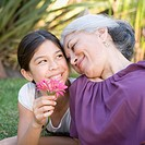 Granddaughter showing flower to grandmother
