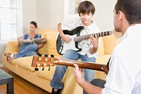 Father and son playing guitars at home