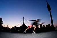 Blured picture of an fast driving sport inline skater with helmet in the front of the scenery of the olympic tower and the olmpic stadion in the mood ...