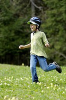 One eight-year-old girl running down a meadow in spring