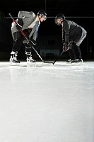 Two businessmen playing ice hockey