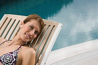 Woman relaxing by a swimming pool