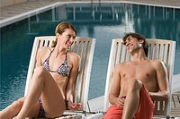 Couple relaxing by swimming pool