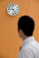 Office worker looking at a wall clock (thumbnail)