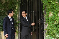 Chinese businessmen outside a house
