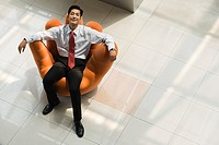 Chinese businessman relaxing in an armchair