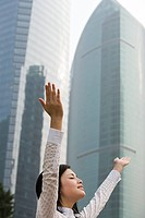 Woman with arms raised near skyscrapers