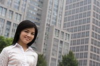 Smiling businesswoman near an office building