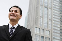Smiling businessman near a skyscraper