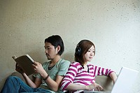 Young couple with book and laptop
