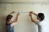 Young couple measuring wall