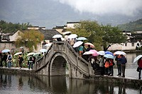 China, Anhui Province, Hongcun village, bridge, people with umbrellas