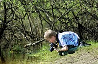 10 year old boy observing life in the water and photographing on a pond edge