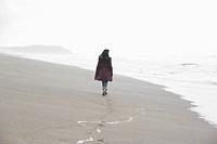 Woman walking on sandy beach rear view